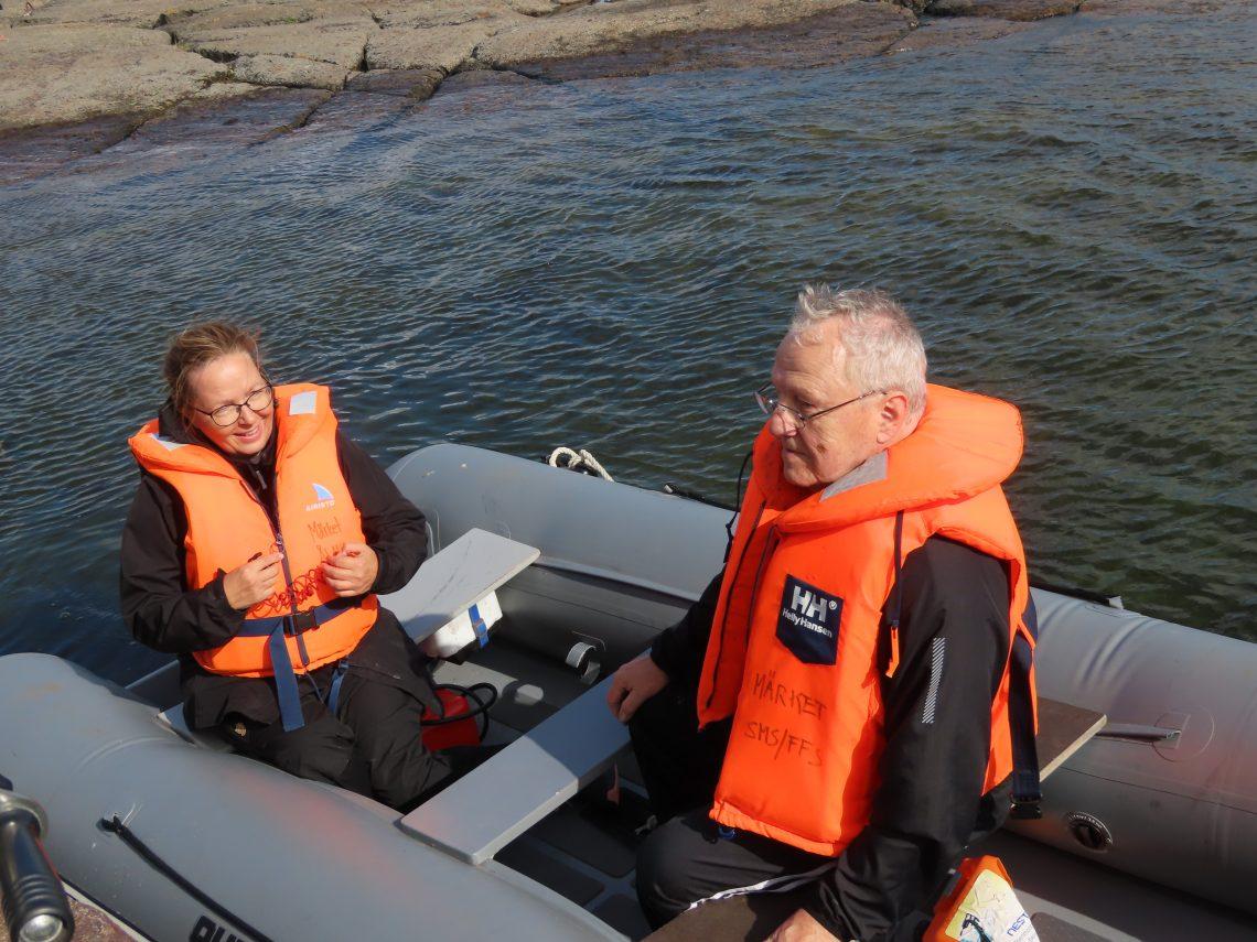 Mies ja nainen veneessä pelastusliivit päällä