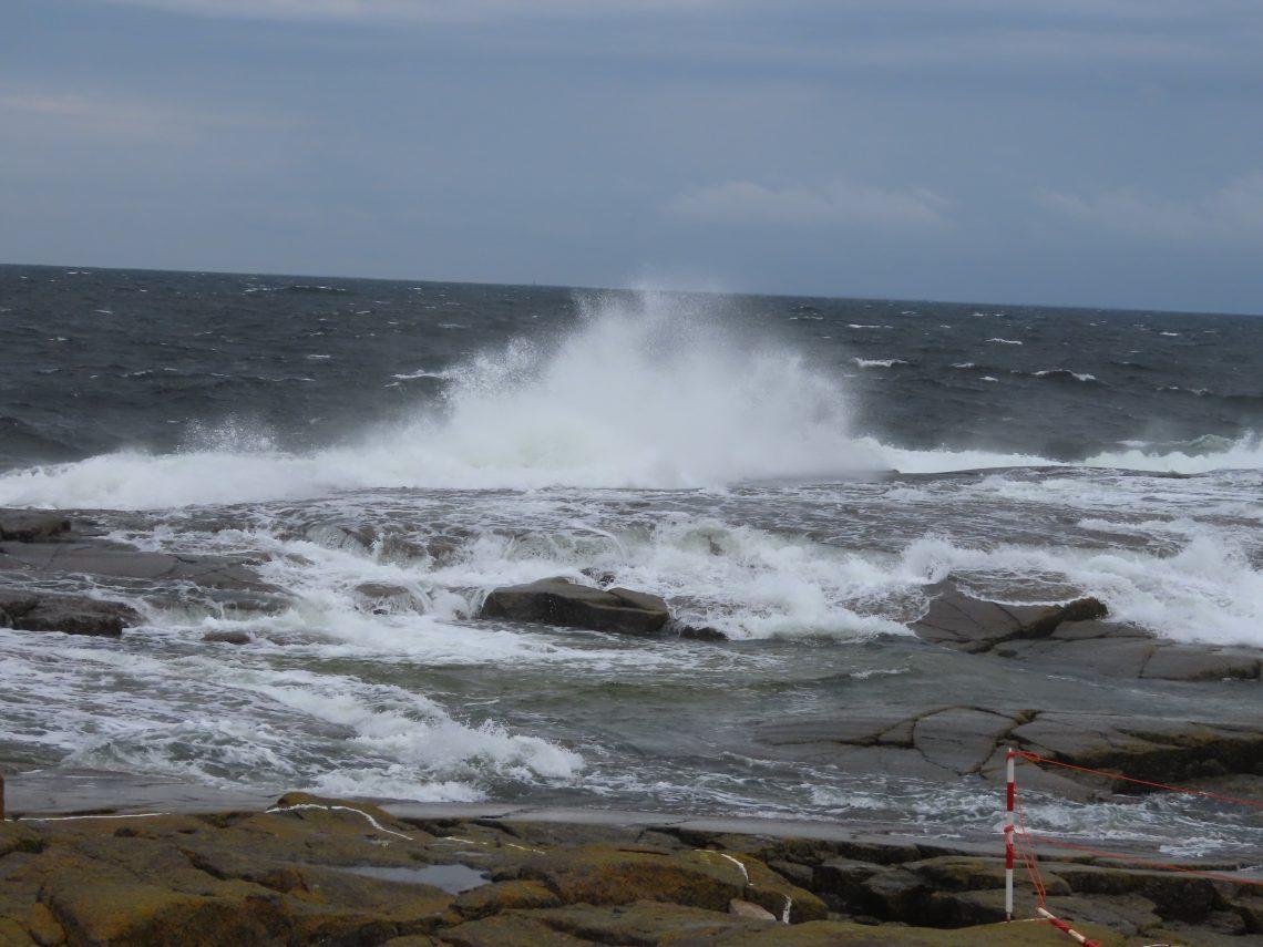 Meren aallot vyöryvät kovassa tuulessa yli luodon