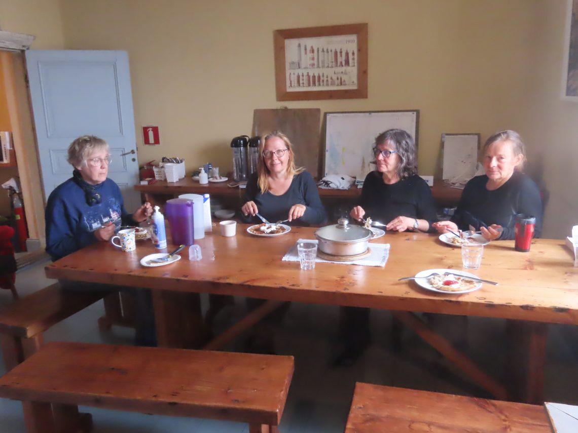Neljä naista istuu pöydän ääressä syömässä lettuja
