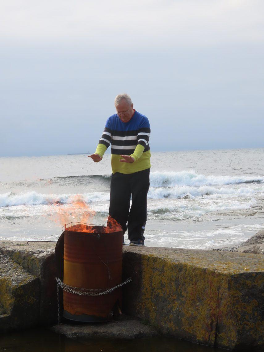 Mies polttaa roskia tynnyrissä