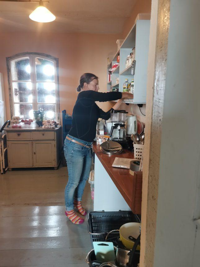 Nainen siivoamassa keittiön hyllyjä