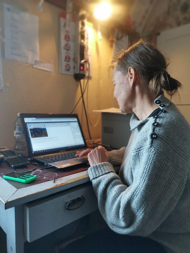 Nainen istuu tietokoneen edessä