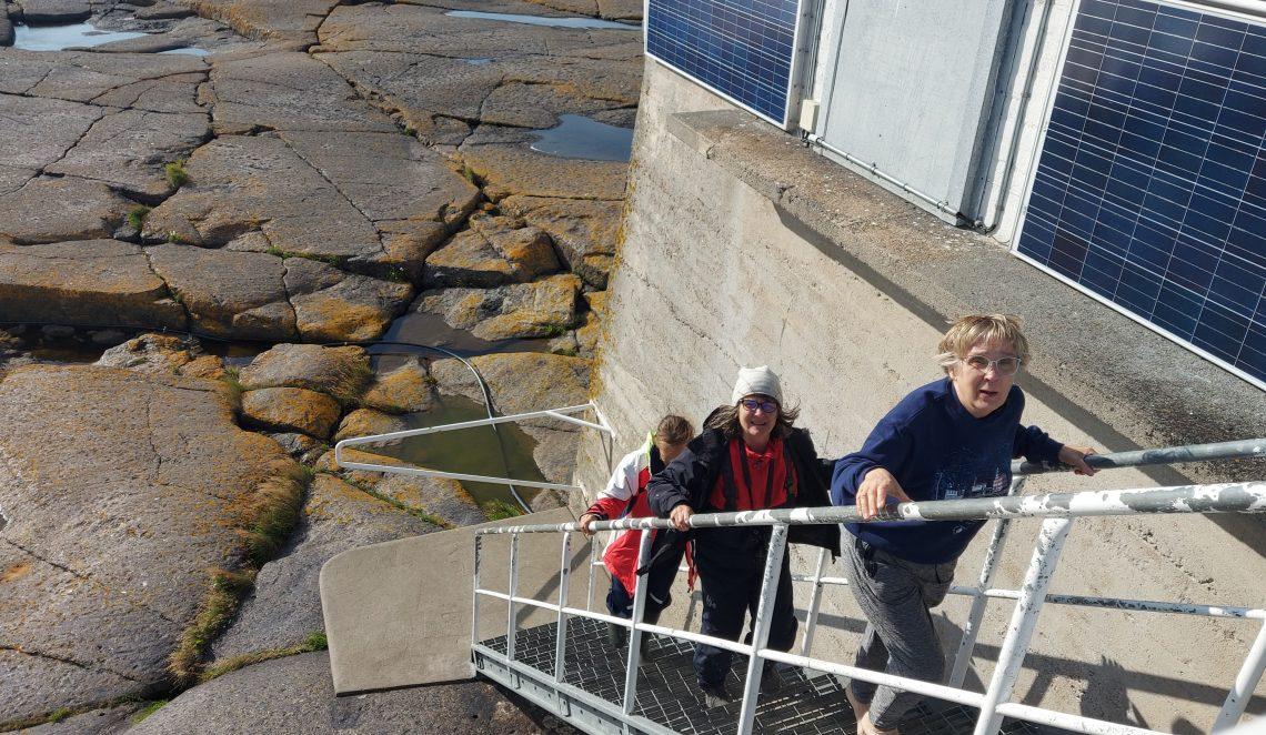 Kolme naista kiipeää ylös portaita