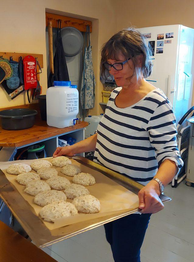 Nainen leipoo sämpylöitä